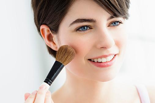 Germany, Bavaria, Munich, Young woman using blusher brush, close up